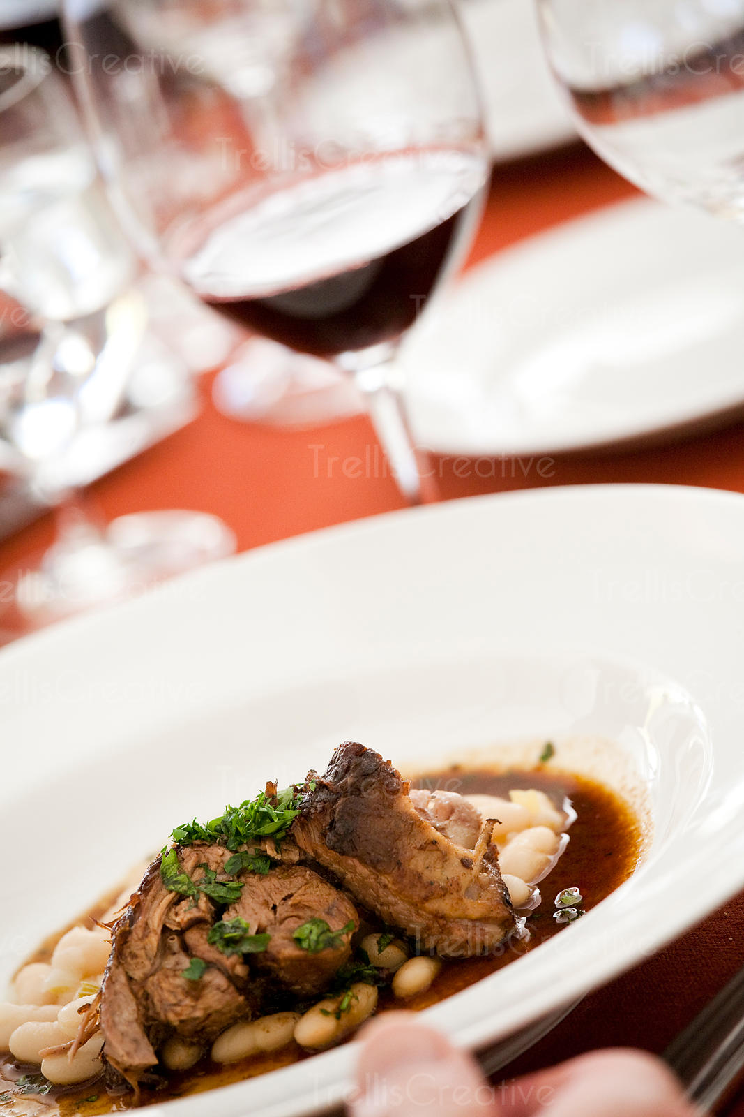 Braised beef short ribs over fresh navy beans in a red wine reduction sauce paired with a glass of cabernet sauvignon