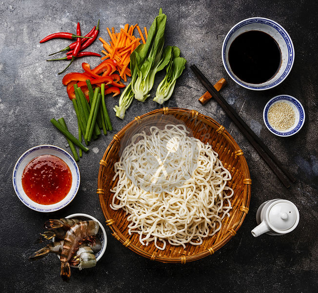 Raw udon noodles in bamboo basket and ingredients for cooking asian raw udon noodles in bamboo basket and ingredients for cooking asian food with tiger shrimps greens vegetables spices on dark background forumfinder Image collections