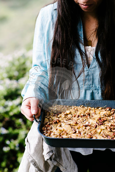 Woman holding baked granola cereal on a farm.