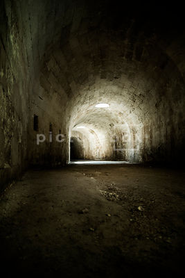 An atmospheric, low perspective image of a darkly lit underground tunnel / bunker stretching off into the distance.