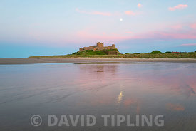 Full moon rising over Bamburgh Castle Northumberland June