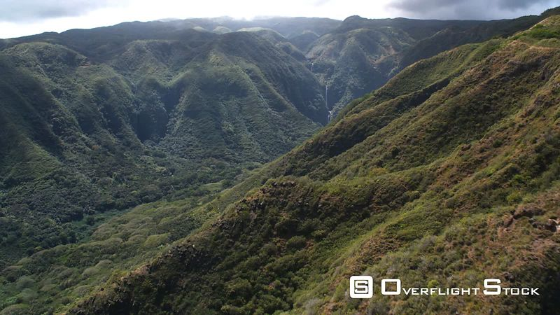 Over steep forested hills to narrow valley and distant waterfalls on Molokai.