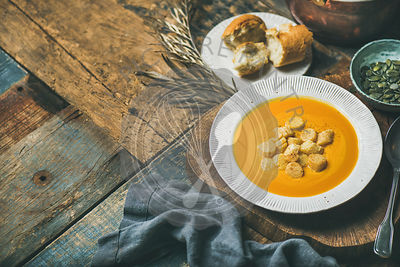 Fall warming pumpkin cream soup with croutons and seeds on board over rustic wooden background, copy space