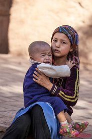 Uyghur girl with child crying, Xinjiang, China