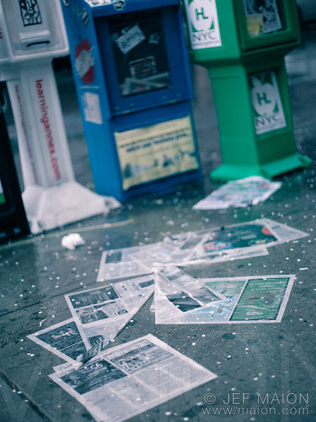 Newspapers on wet pavement