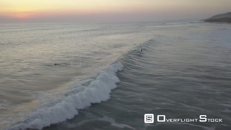 Aerial view of surfers and swimmers on ocean waves, filmed by drone, at sunset, Costa Rica - drone stock footage