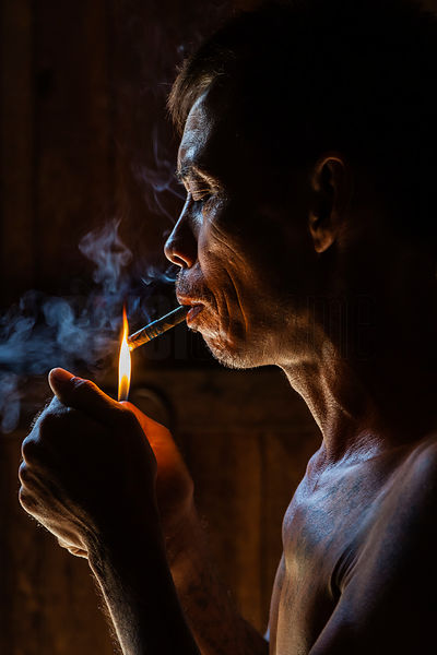 Portrait of Blacksmith Min Naing Lighting a Cheroot