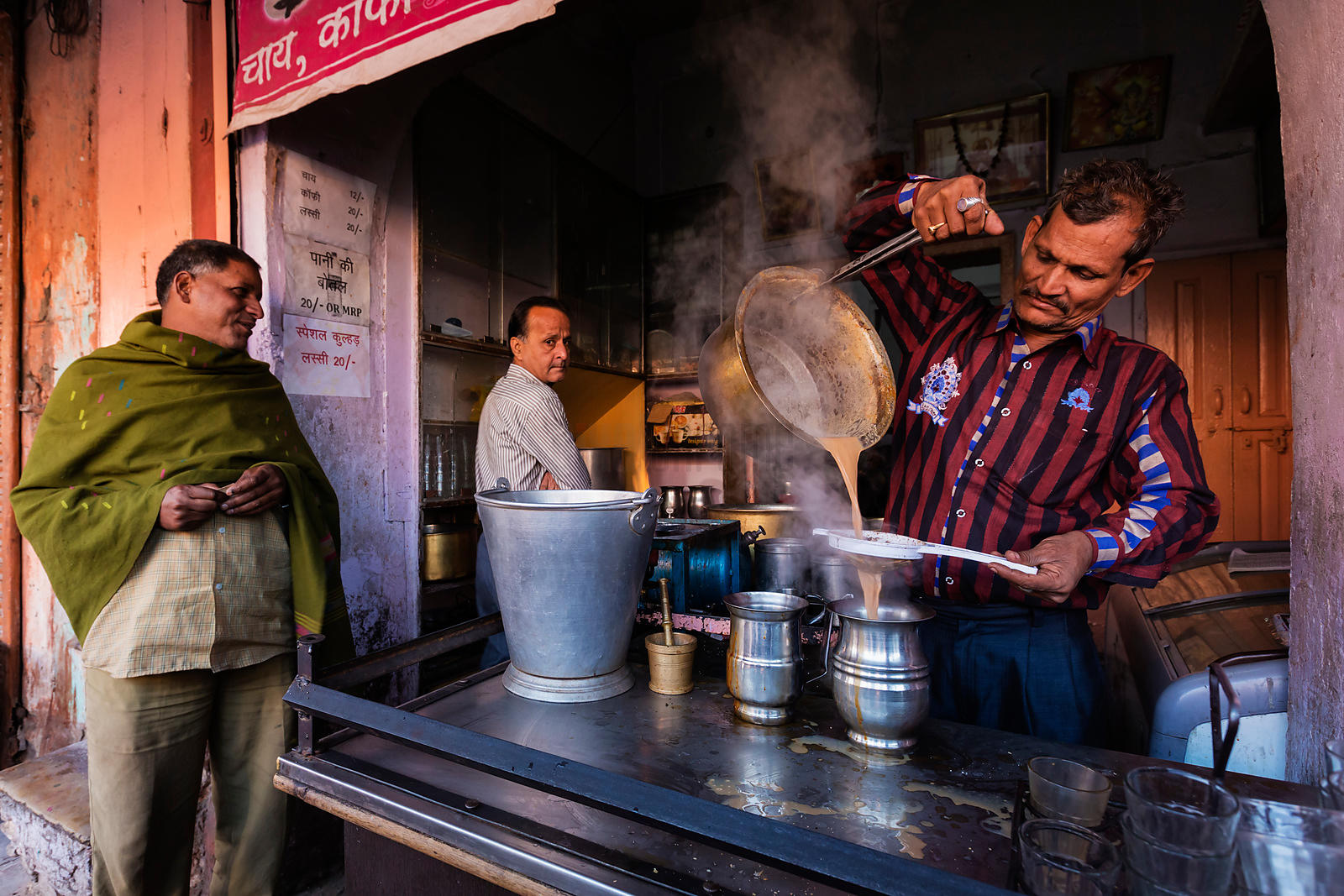 Tea Seller Pouring Chai into a Stainless Steel Jug