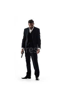 A mystery man in a suit, standing with a gun and looking down – shot from low level.