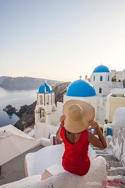 Woman admiring the village of Oia, Santorini, Greece
