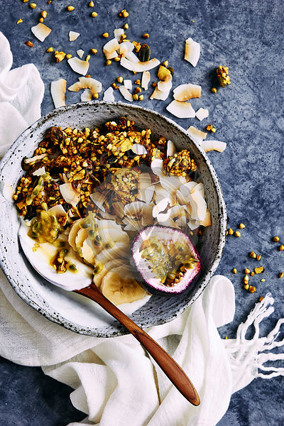 Healthy breakfast bowl of yogurt, turmeric glutin free muesli clusters, toasted coconut, fresh fruit and honey comb.