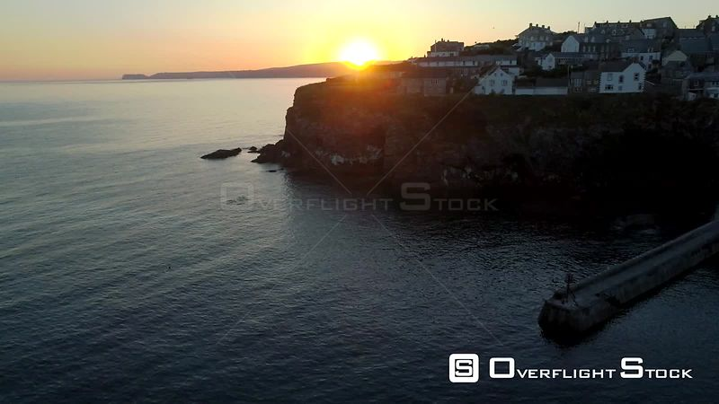 Drone rises from harbor wall of Port Isaac in Cornwall to reveal surnrise