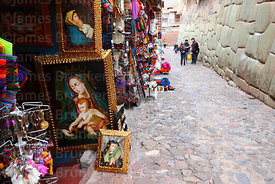 Religious art for sale in street with Inca walls, Cusco, Peru