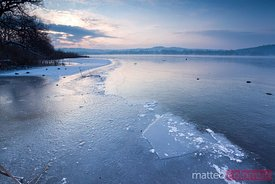 Sunrise over frozen lake in winter