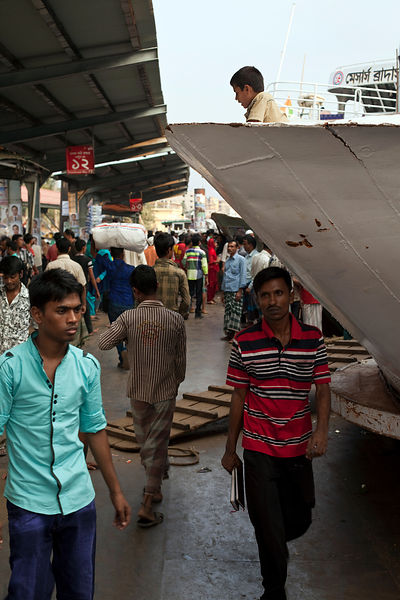 Bangladesh - Dhaka - A boy waits on the prow of a ferry while people on the quayside rush past at Sadarghat