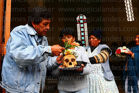 A woman has her skull blessed with holy water as she leaves church after mass, Ñatitas festival, La Paz, Bolivia
