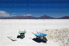 Wheelbarrows for moving salt on the Salar de Coipasa, Tata Sabaya volcano in background, Oruro Department, Bolivia