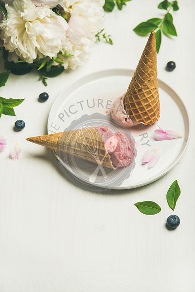 Pink strawberry and coconut ice cream scoops, sweet cones and peony flowers, copy space