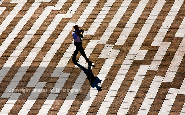 A businessman crosses the bridge from Paradise Forum to Centenary Square, Birmingham, West Midlands.