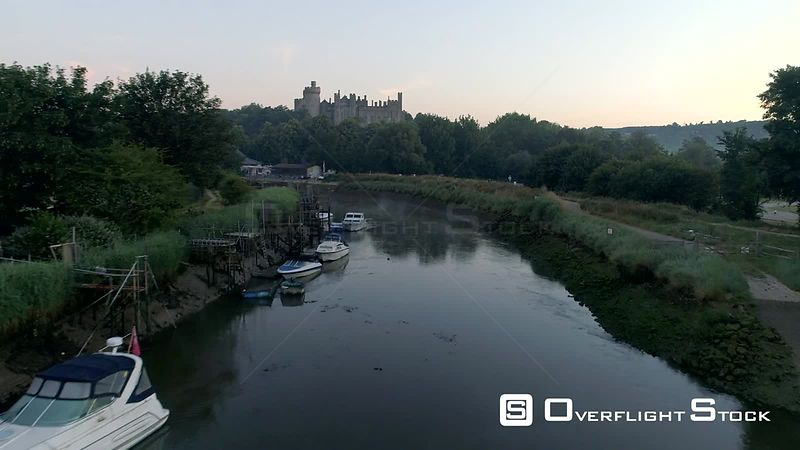 Drone flies along Arun river, rising to show Arundel Castle in a misty dawn