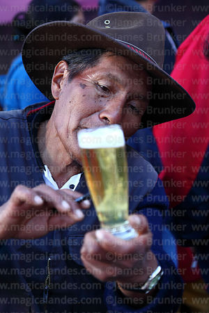 Shaman or yatiri reading future from shapes formed by an egg white that has been dropped in a glass of beer, La Paz, Bolivia