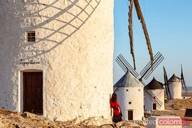 Woman near windmills on the Don Quixote route, Spain