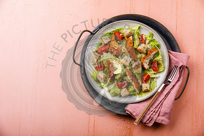 Caesar salad with Chicken breast meat on metal tray on pink background copy space