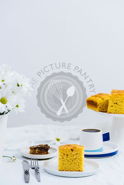 A slice of pumpkin cornbread on a white plate photographed on a white background from front view. A fork and a knife, a piece of honeycomb, white flowers, coffee and a cake stand with cornbread slices accompany.