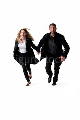 A man and a woman running hand in hand – shot from mid level.