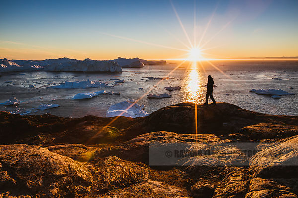 Silhouette of a man exploring the Ilulissat Icefjord at sunset