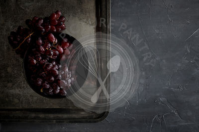 Fresh, red grapes in on a patinated metal tray on a dark countertop. Dark, moody, natural lighting.