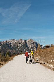 A man and woman with child in a pushchair  hiking in the Fanes Sennes Prags Nature Park near Schluderbach Carbonin in the South Tyrol, Italy.