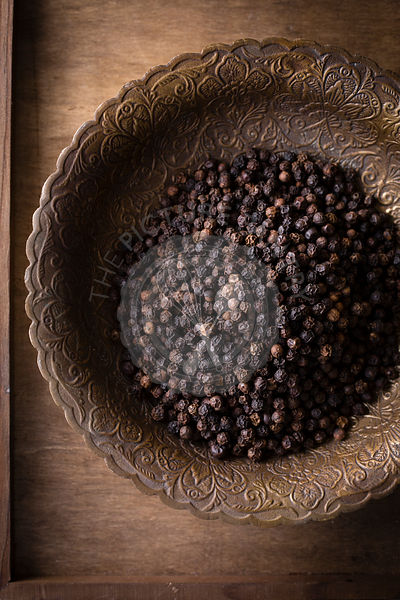 Black peppercorns ina vintage brass bowl on top view
