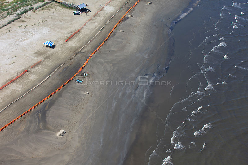 Aerial view of Slickbar oil booms on the beach at Grand Isle, used in the clean up and containment of hazardous oil, from the BP Deepwater Horizon spill in the Gulf of Mexico. Jefferson Parish, Louisiana. USA, July 2010.