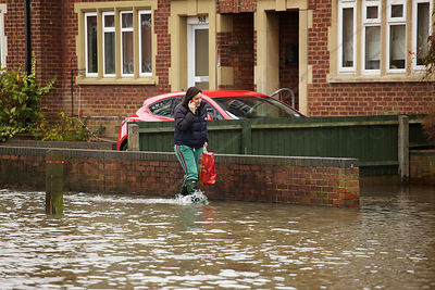 Woman on Phone Walks Along as Flooded Pavement