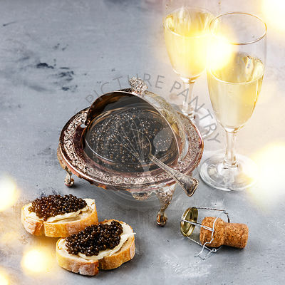 Black caviar in silver bowl, sandwiches and champagne on gray concrete background