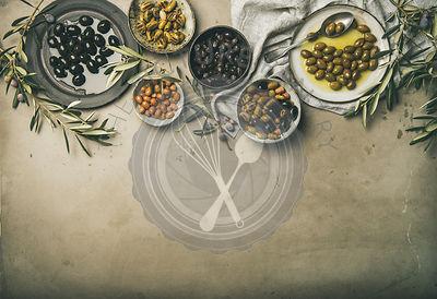 Mediterranean pickled olives and olive tree branches on grey background