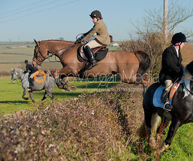Hunt followers jump a hedge in Brooke, Rutland.