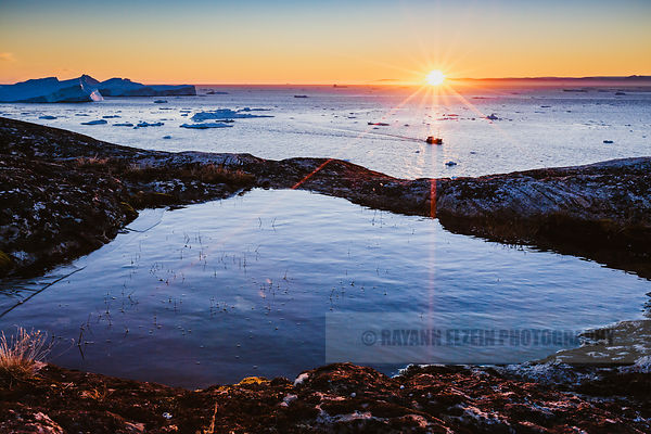 A tourists boat returns to Ilulissat from their iceberg tour under a magnificent sun