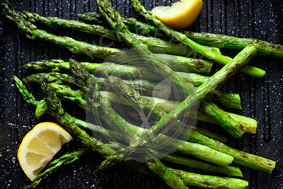 Char-grilled asparagus with lemon wedges.
