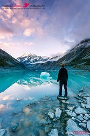 Hiker near glacial lake looking at Mt Cook at sunset, New Zealand