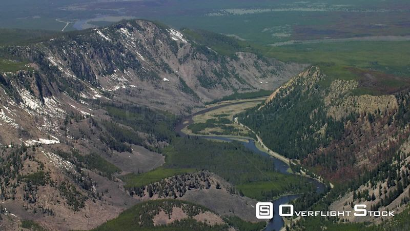 The madison river winds through spring green meadows and a steep canyon on the western edge of Yellowstone National Park, as the Henry's Lake mountain range towers in the distance