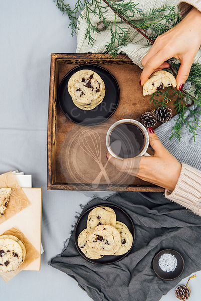 A woman holding a cup of coffee and a half eaten cookie in a breakfast tray  photographed from top view. More cookies on a black plate and on some books, pine tree branches and a small bowl of sea salt accompany.