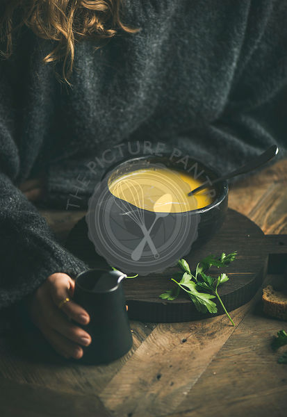 Woman in grey winter sweater eating sweet corn soup