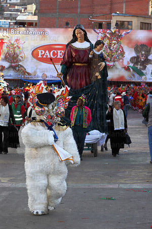 Bear dancer taking part in the Diablada dance, Statue of Virgen del Socavon behind, Oruro Carnival, Bolivia