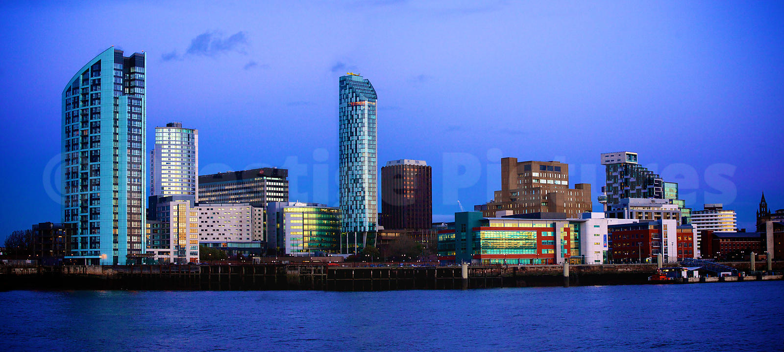 The Setting Sun reflecting on Buildings along the Liverpool Waterfront at Dusk Viewed from across The Mersey