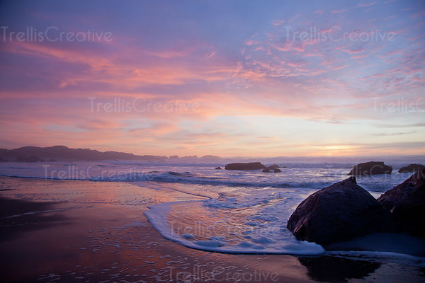 Gentle waves lap at the beach with a colorful sunset