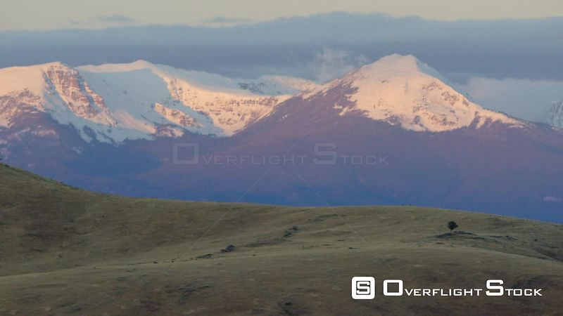 The early morning sunrise highlights the snow-covered summits of the Spanish Peaks in the Madison mountain Range near Bozeman, Montana