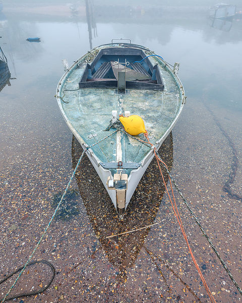 An old yacht moored on a creek in misty, calm conditions. Exmouth, Devon, UK