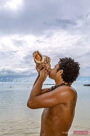 Local tahitian man blowing a conch shell, Moorea, French Polynesia